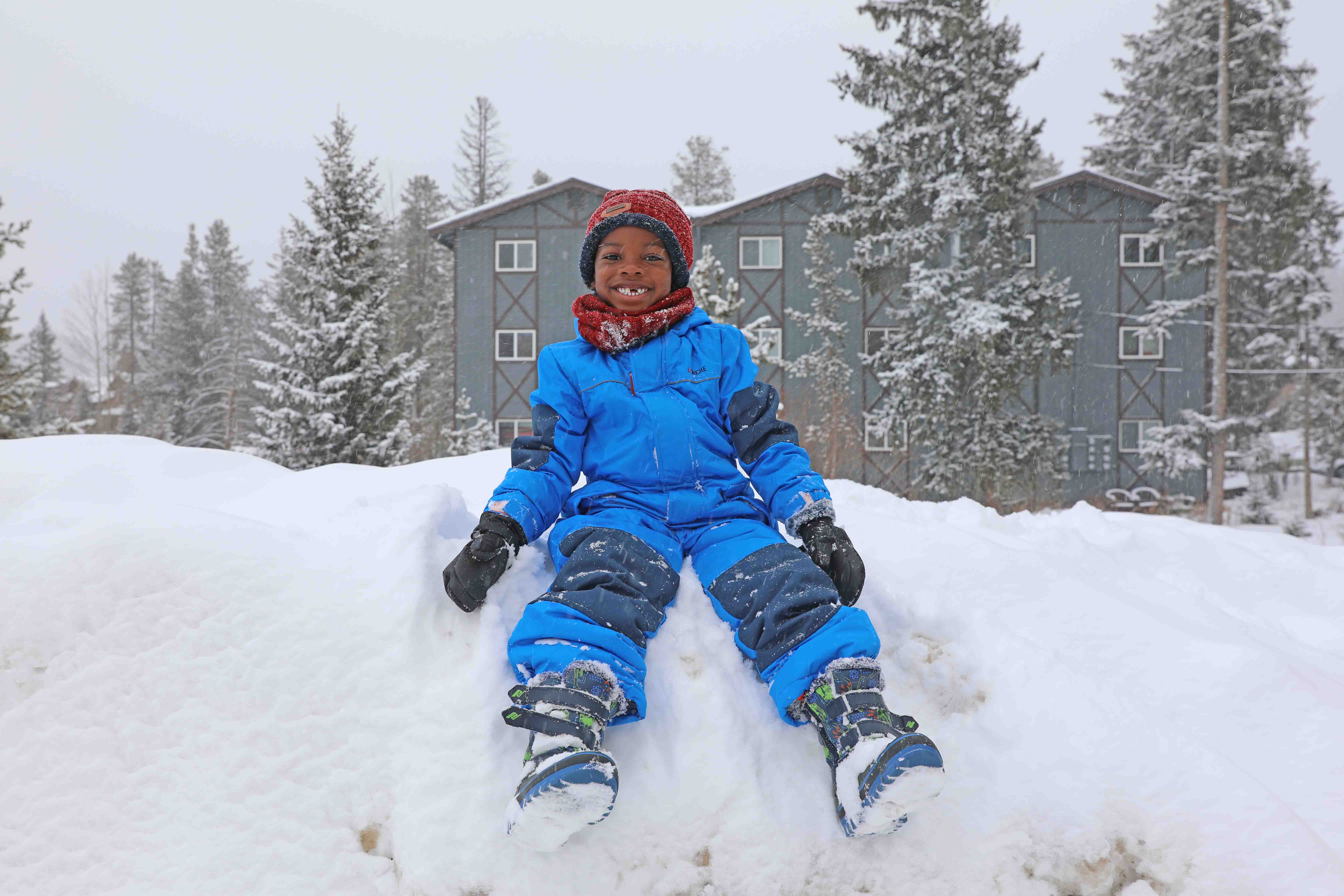 A little boy sitting on top of a hill of snow in his winter gear, including a snowsuit, snow boots hat and gloves.