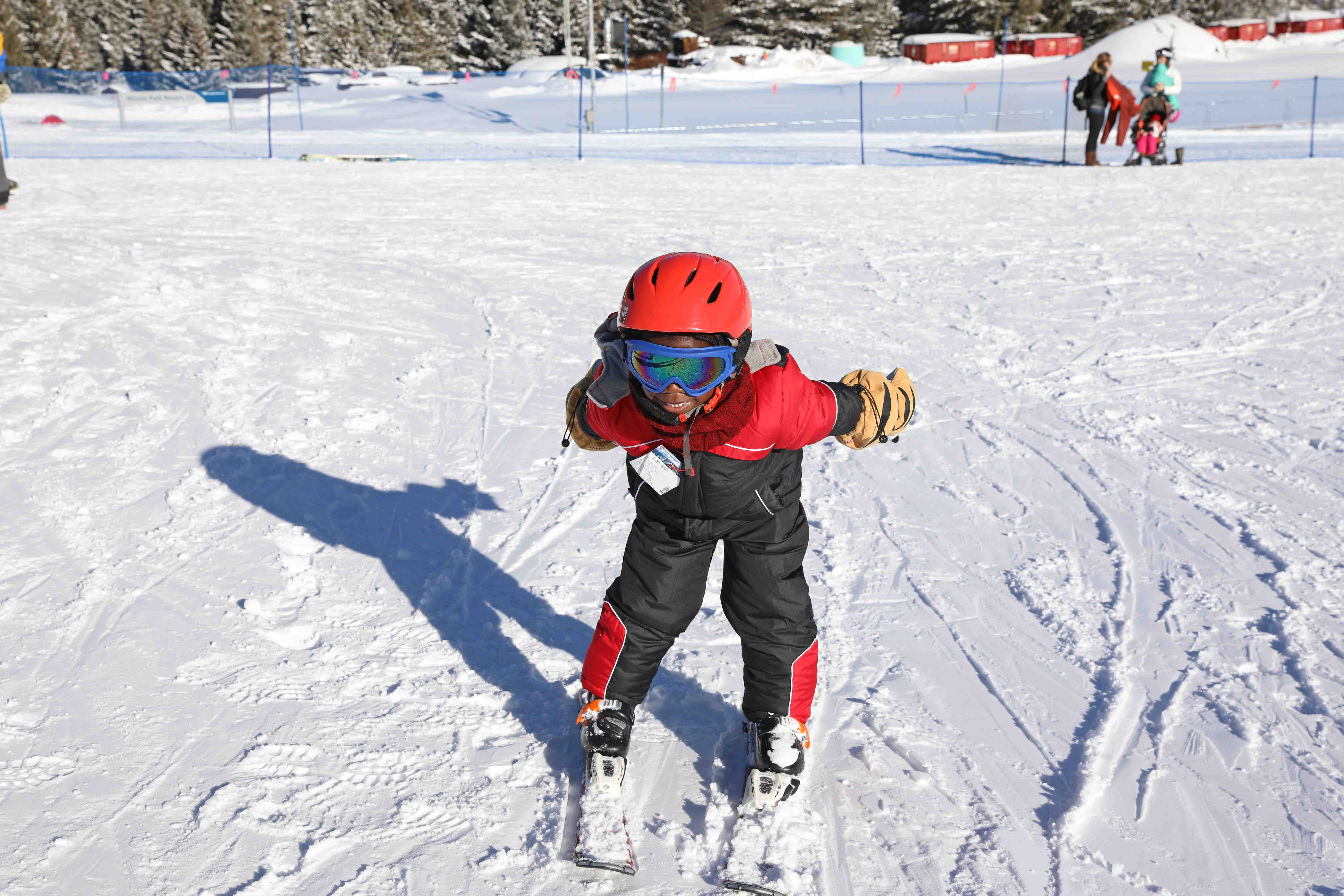 A little boy in a red and black snowsuit standing on a set of skies on a ski slope with all of his snow gear for kids