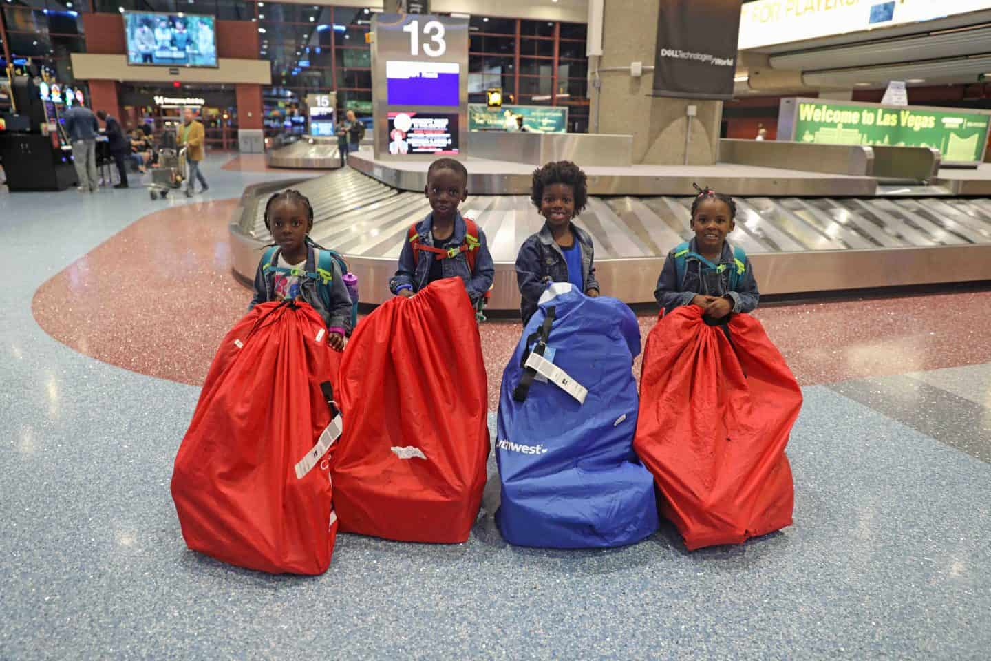 4 kids with their carseats in the baggage claim area of an airport - how to avoid extra fees when flying spirit airlines