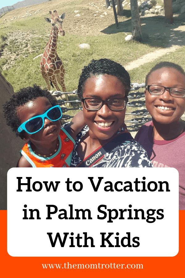 Mom and two kids smiling in front of a giraffe - how to vacation in palm springs with kids