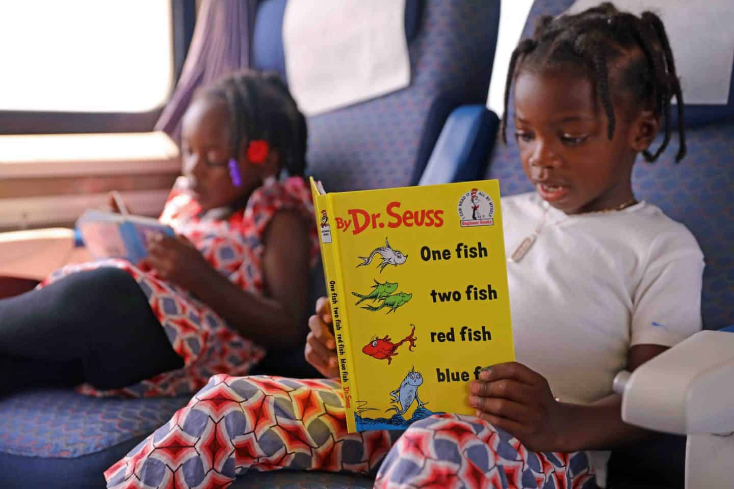 Two girls reading Dr. Suess books on the Los Angeles To San Diego Amtrak Train