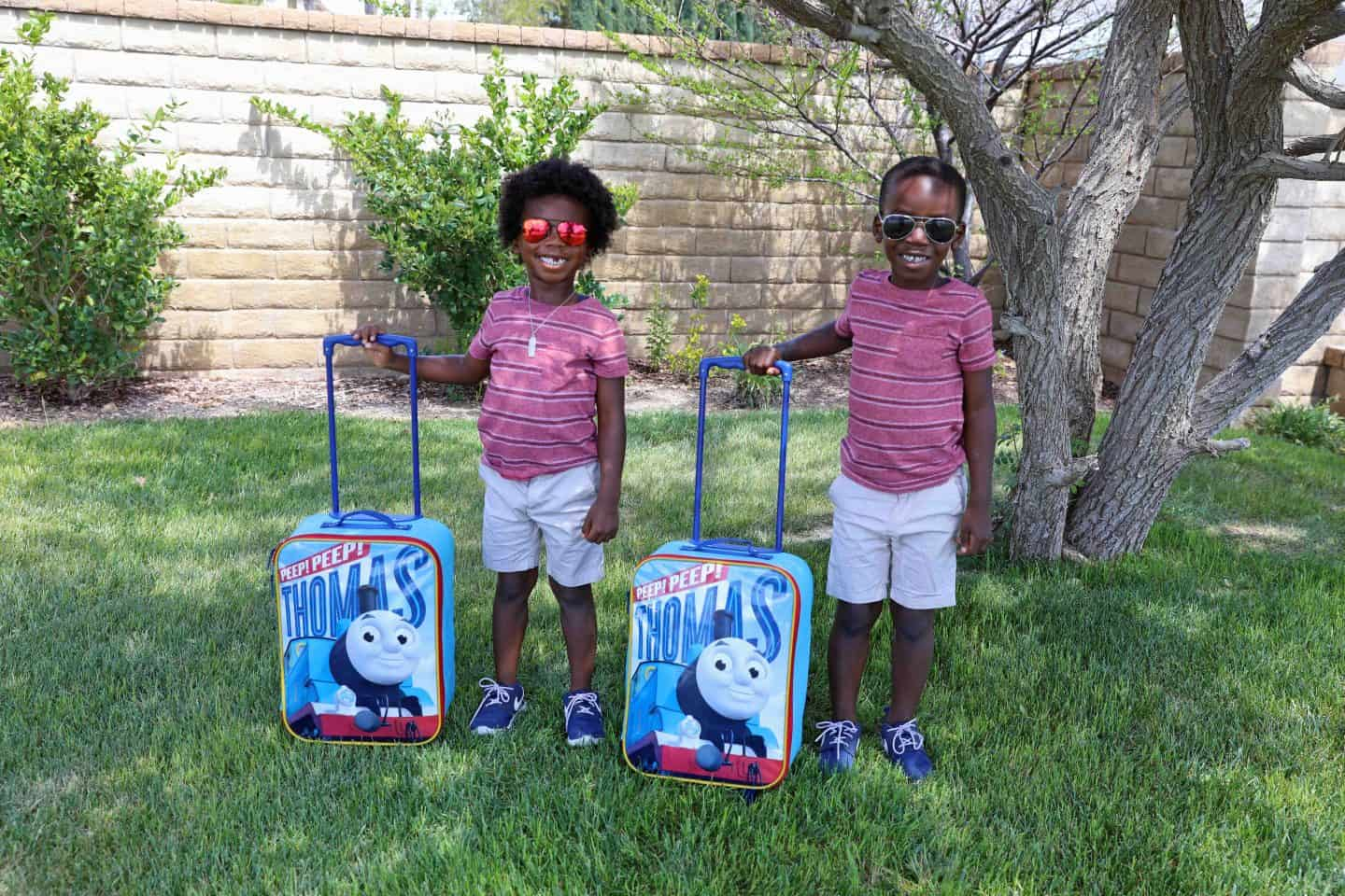 two children in sunglasses with Thomas the Train suitcases - how to vacation in palm springs with kids
