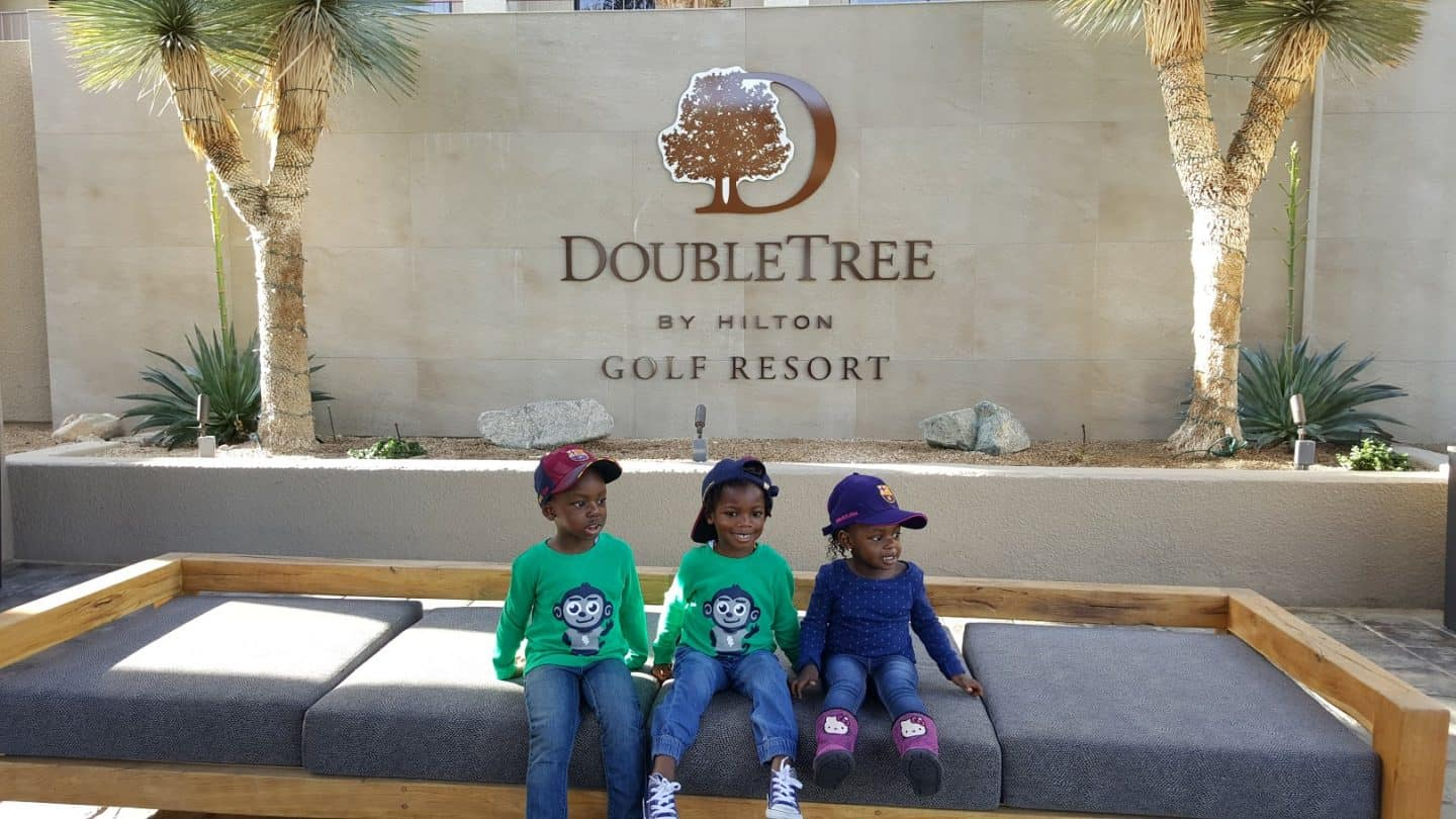 3 kids sitting on a bench in front of the Doubletree by Hilton resort in Palm Springs