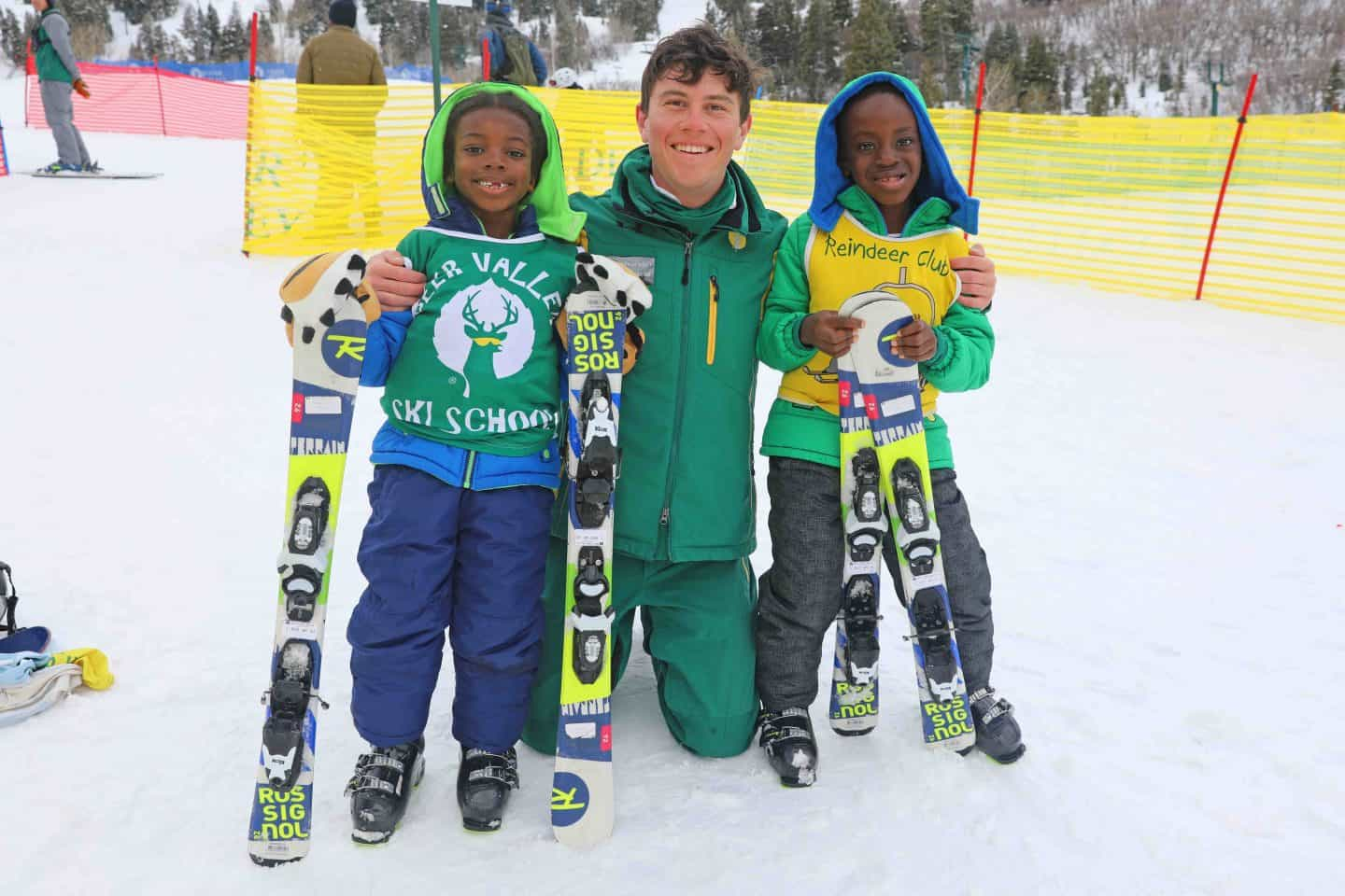 black kids receive ski lesson from instructor