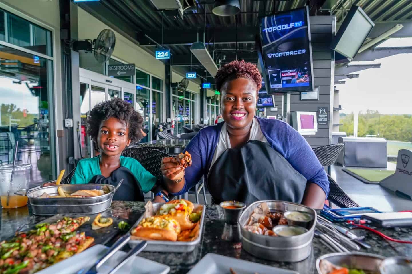 enjoying food at topgolf Overland Park