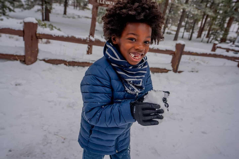A boy making a snowball.