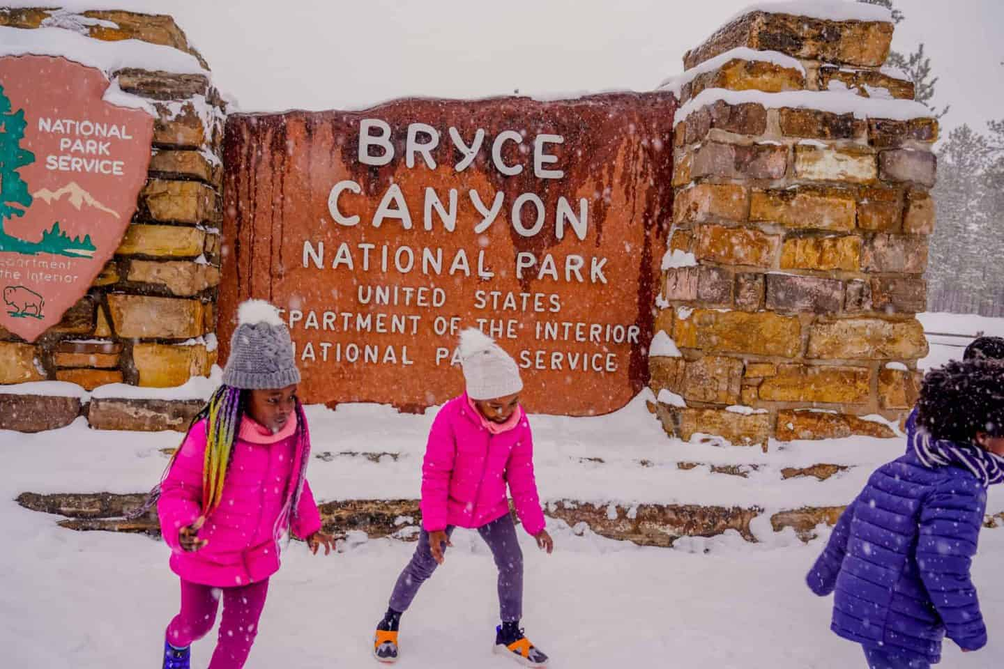 Children playing in front of the Bryce Canyon National Park sign.