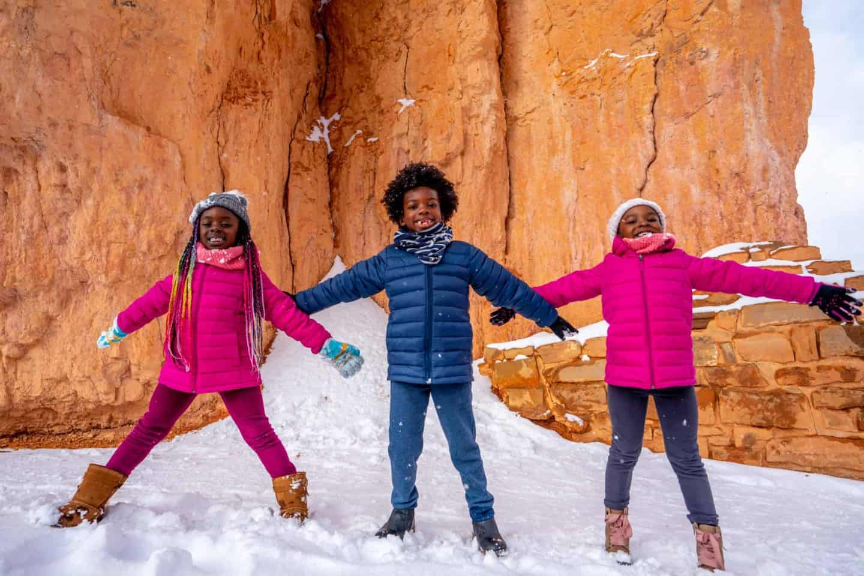 Three children posing at Bryce Canyon National Park .