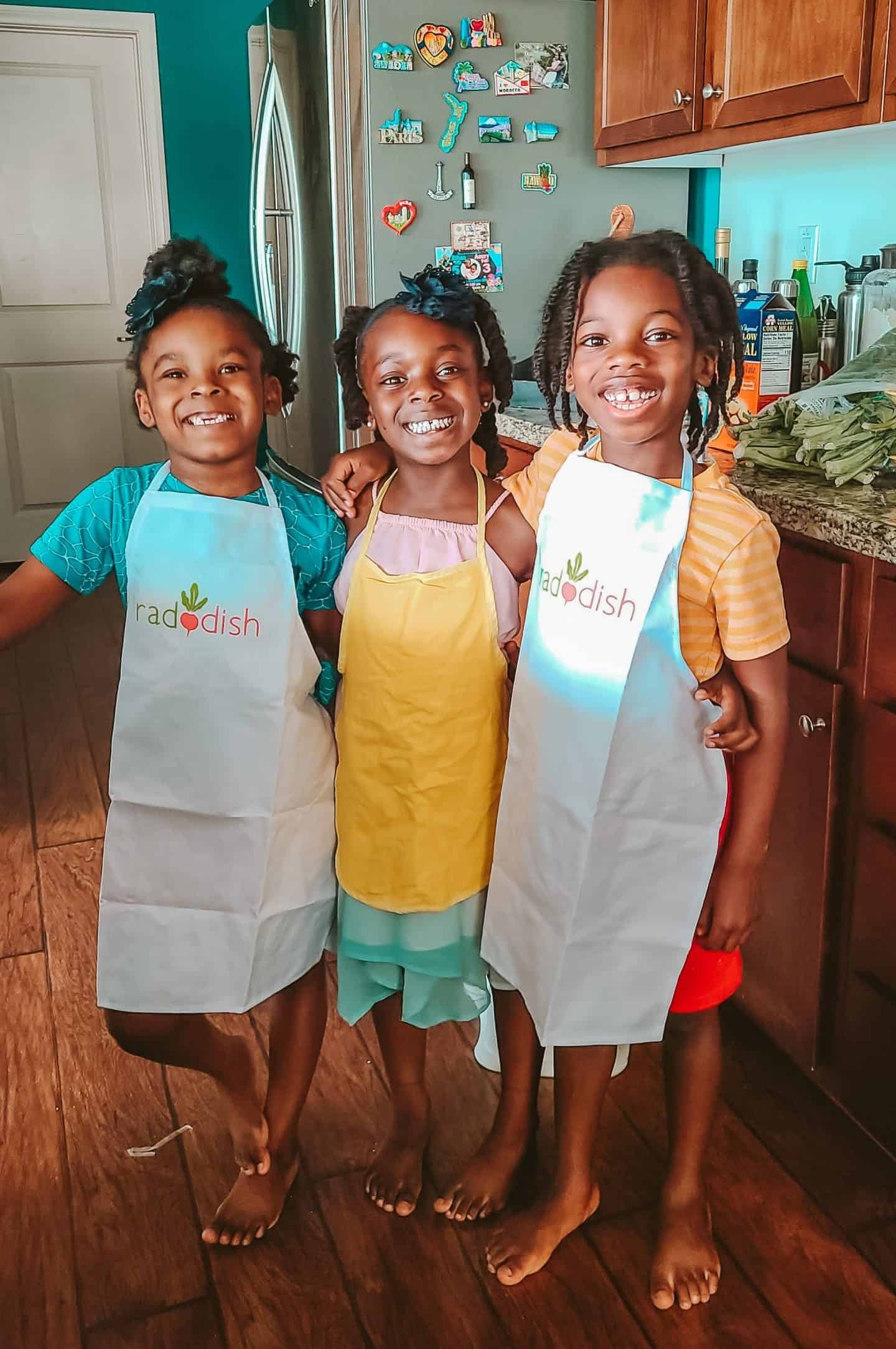 Three young children hug and smile as they get ready to cook and enjoy time socializing together even while home schooled.