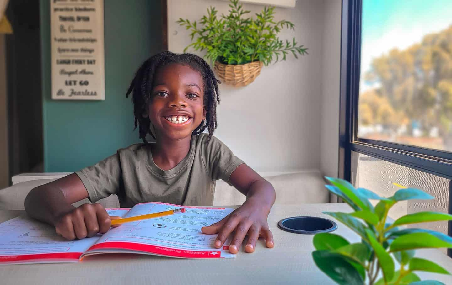A young boy sits at a desk with a school workbook open smiling and holding a pencil enjoying his homeschooling lesson.